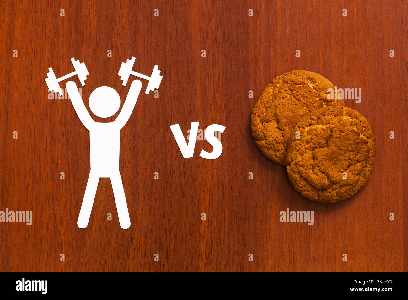 Paper man with dumbbells vs unhealthy food. Abstract conceptual image - Stock Image