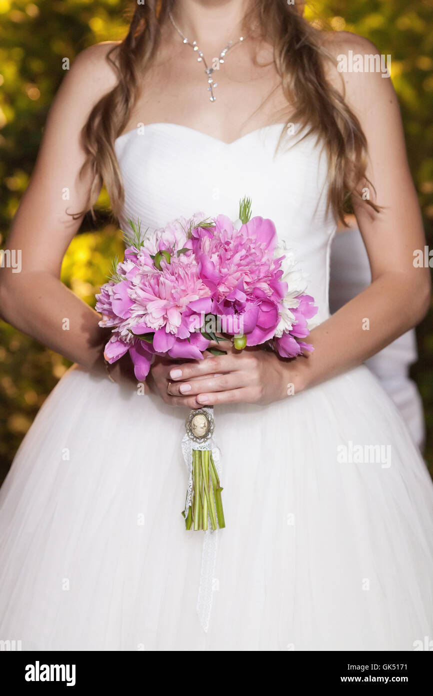 Beautiful pink peony wedding bouquet in bride's hands, closeup Stock Photo