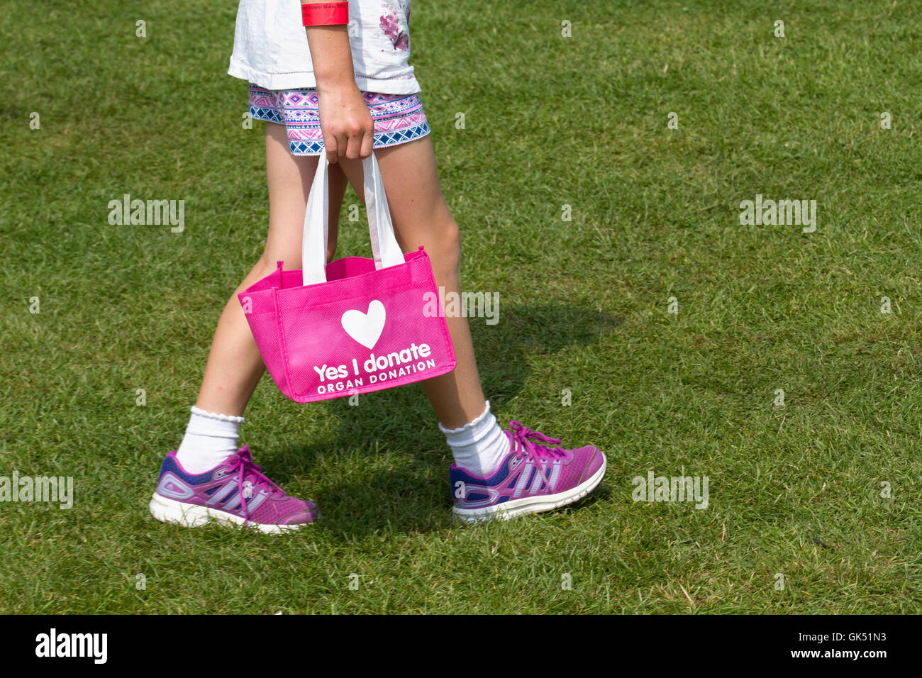 Yes I Donate. Young Evie Pownall, (MR) girl 6 years old carrying 'Yes I donate'  pink bag recommending registering - Stock Image