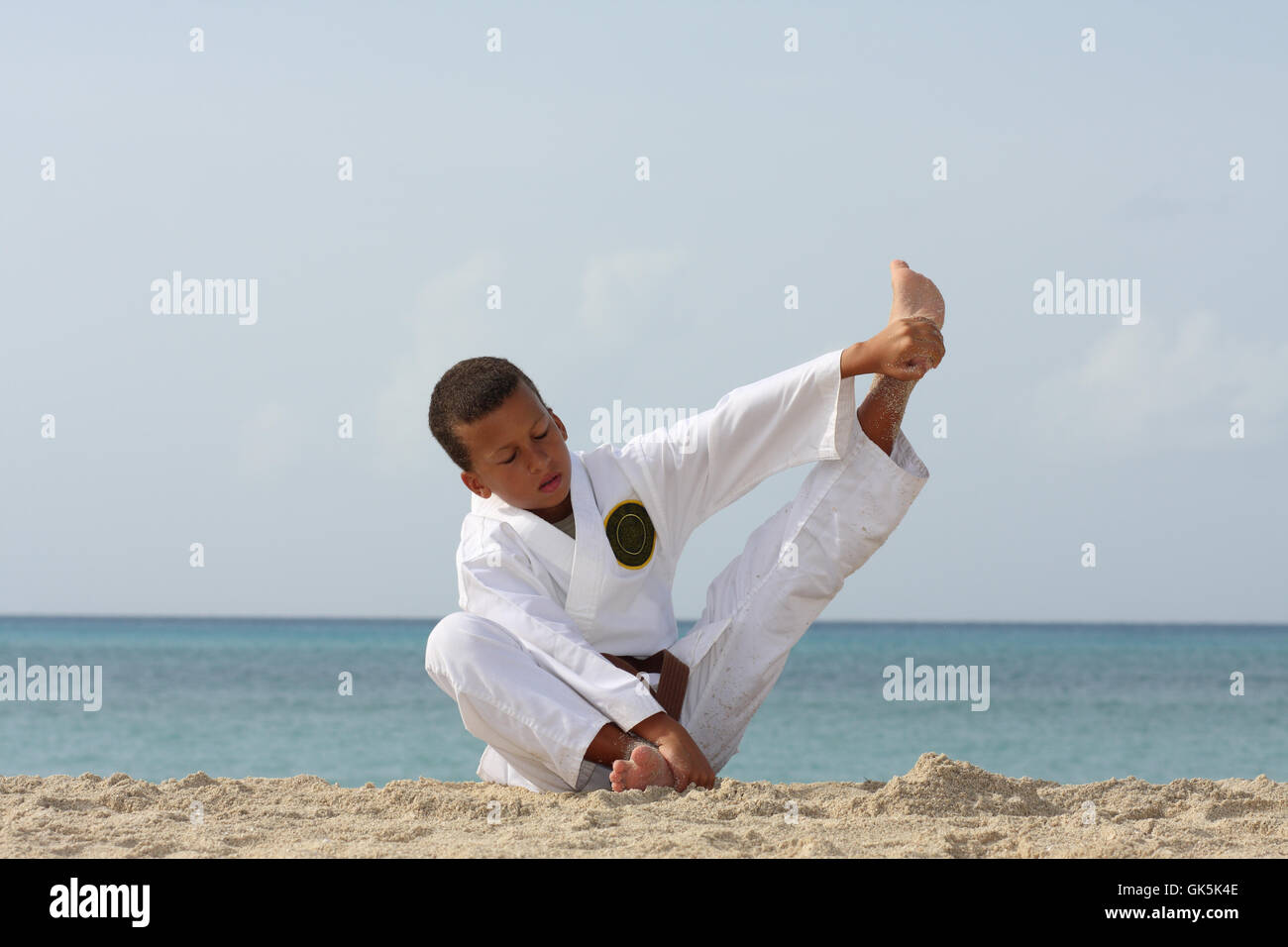 11-years boy doing warming-up before Tae Kwon Do work-out on the Caribbean island beach. - Stock Image