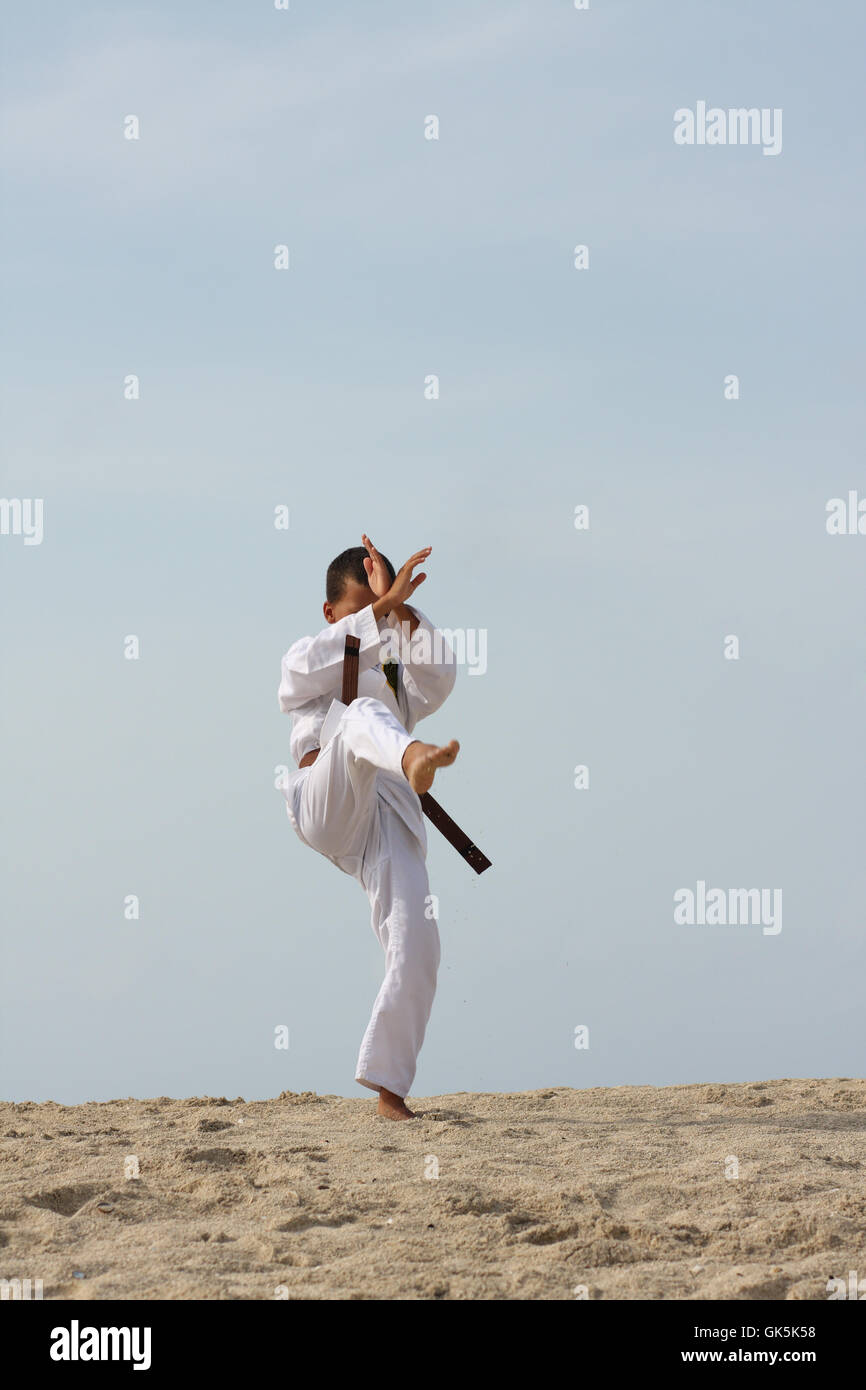 11-years boy doing Tae Kwon Do work-out on the Caribbean island beach. - Stock Image