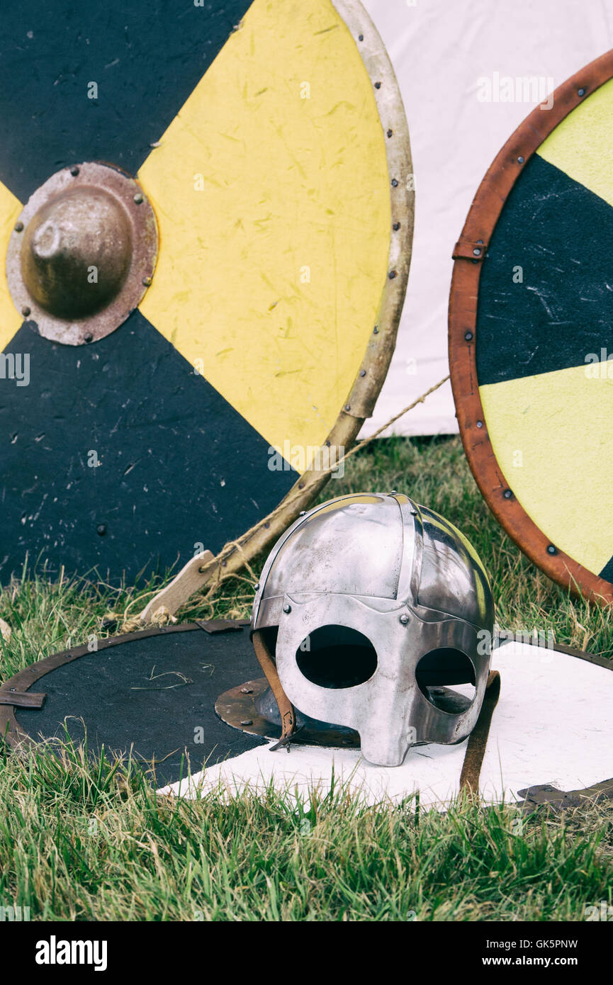 Viking helmet and shields at a living history reenactment at Spetchley Park, Worcestershire, England - Stock Image