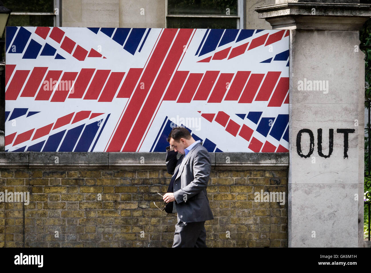 UK Brexit documentary image. A London city worker passes a British union flag wall design. 'OUT' is written - Stock Image