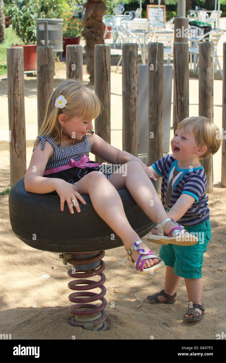 brother and sister siblings playing together on playground at park - Stock Image