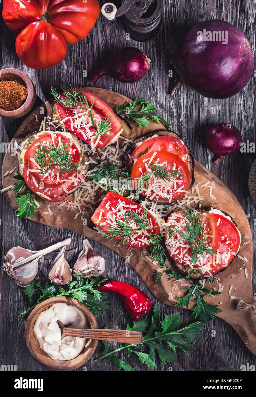 Eggplant and tomato stacks rustic above view - Stock Image