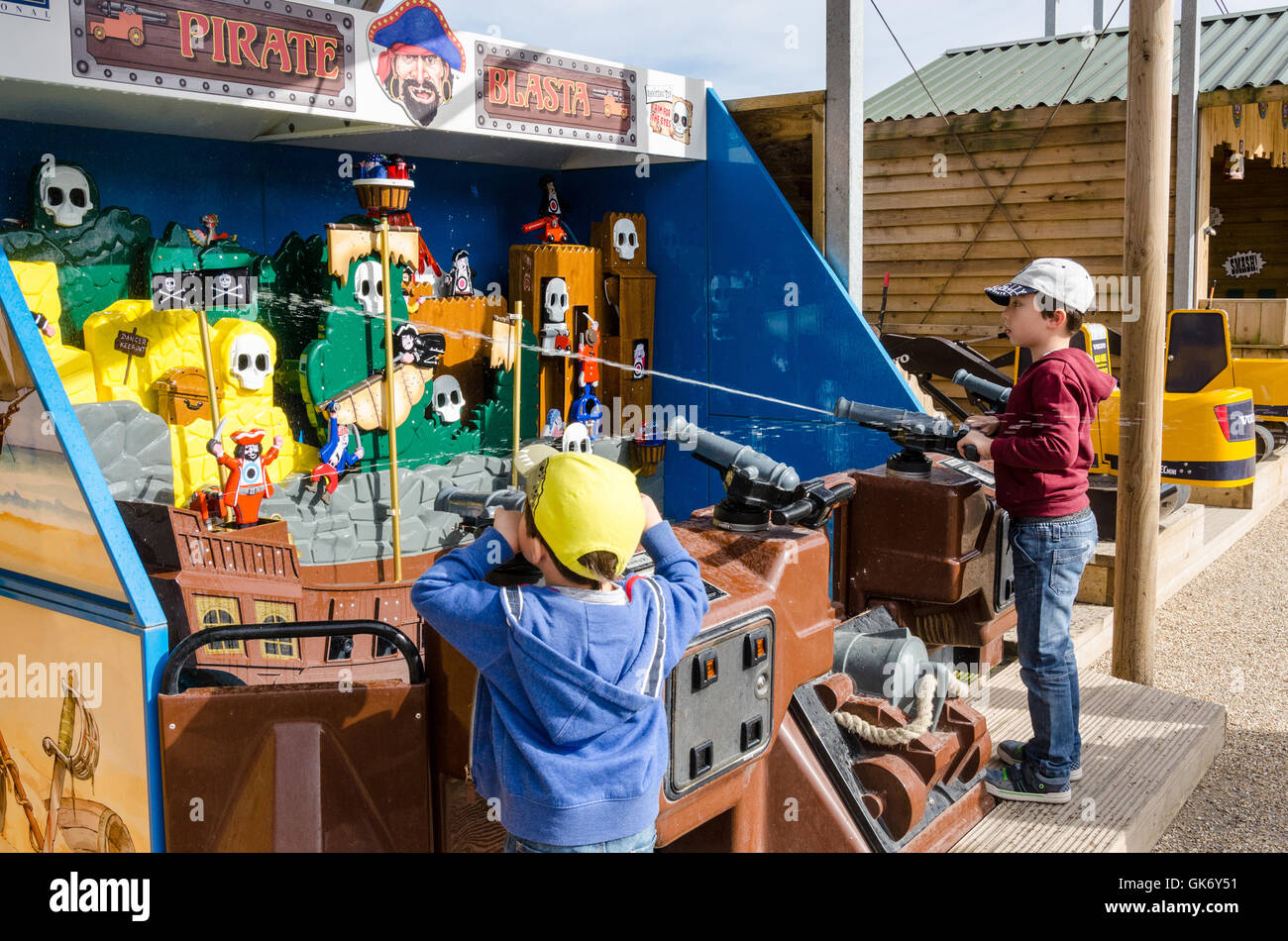 A couple of young brothers play on a water cannon shooting game at the fairground. - Stock Image