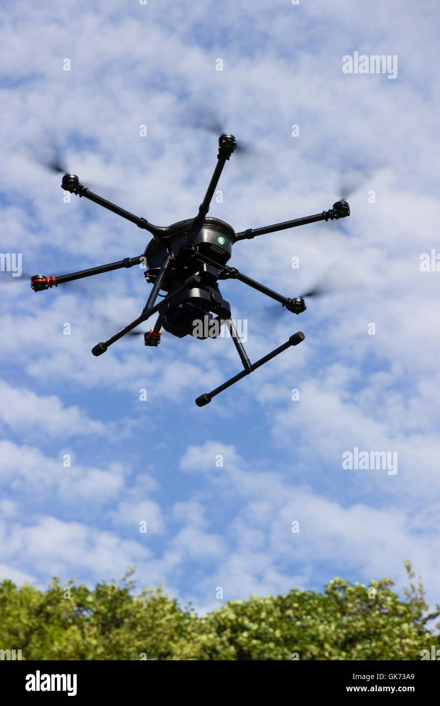 Yuneec Typhoon 920 hexacopter drone with gimbal mounted camera in flight against a cloudy blue sky - Stock Image