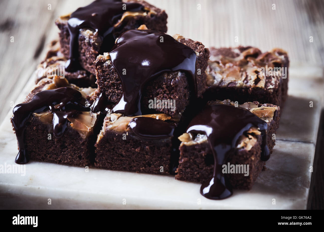 Homemade caramel chocolate brownies with dark chocolate ganache served on marble stand - Stock Image