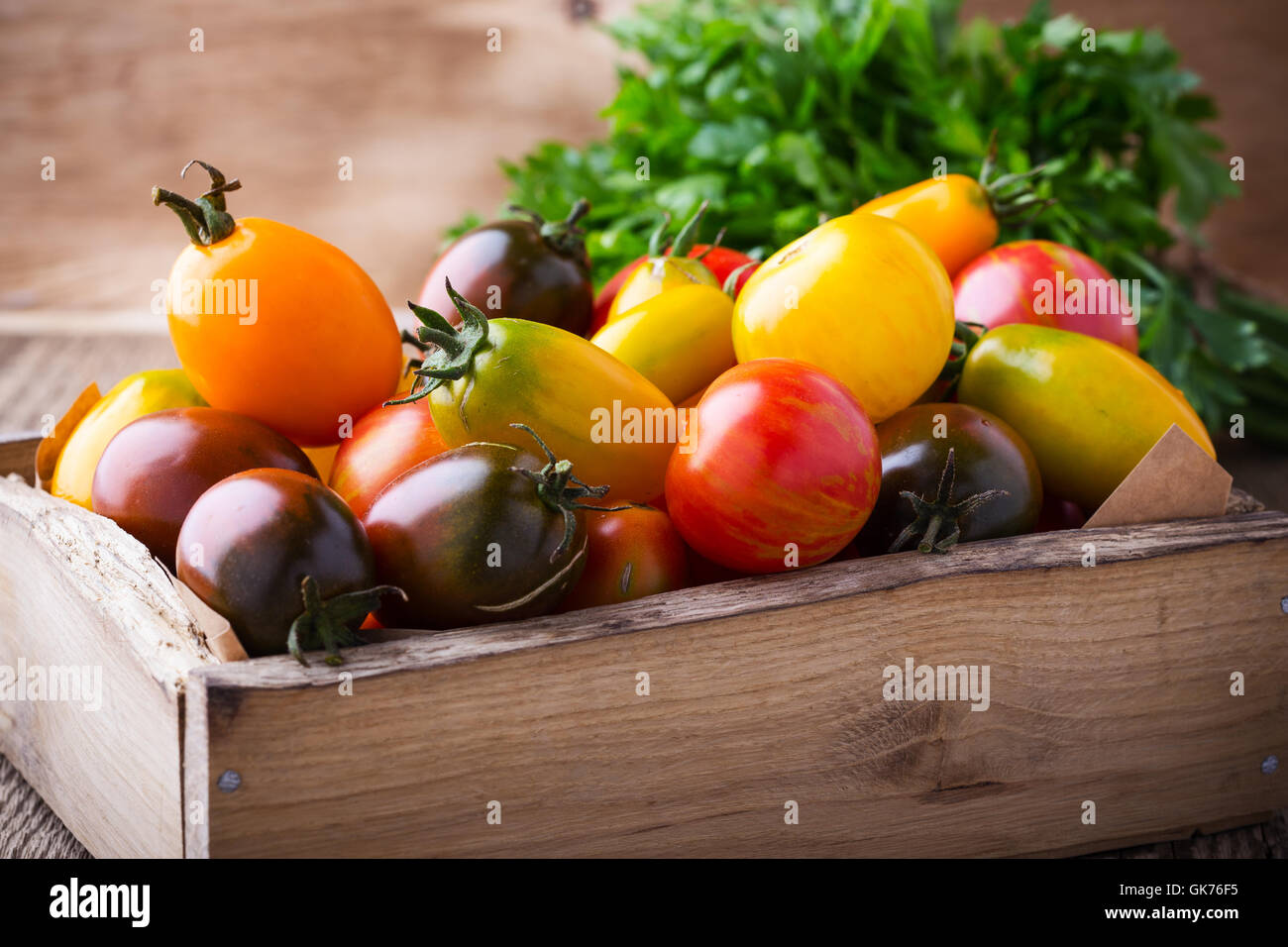 Assorted tomatoes  in wooden box. Composition of colorful vegetables in summer harvest time Stock Photo