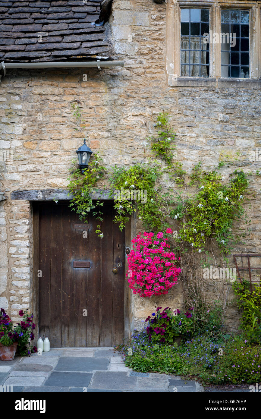 Milk bottles at front door of cottage in Castle Combe, the Cotswolds, Wiltshire, England - Stock Image