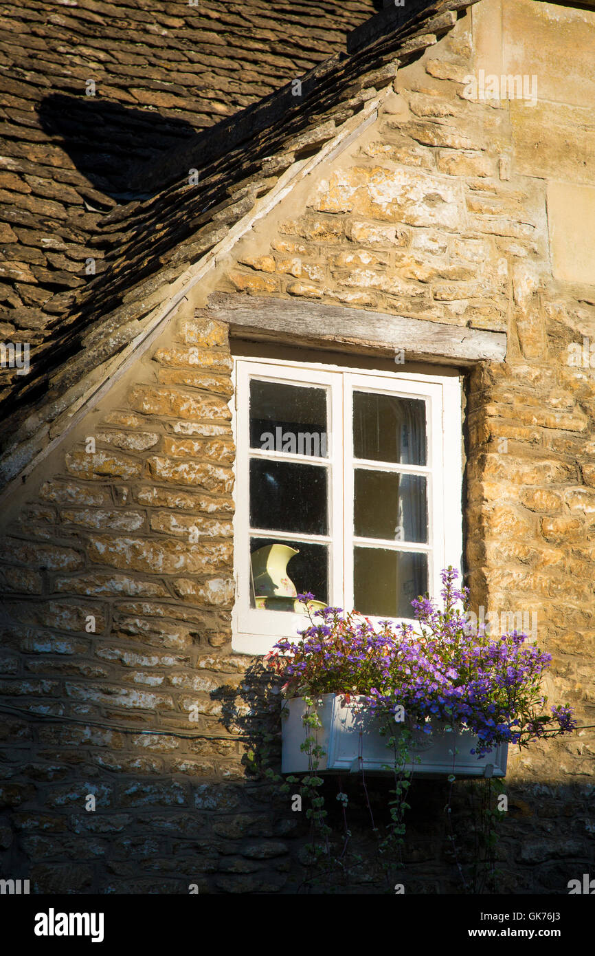 Window and flower box on a cottage home in Castle Combe, the Cotswolds, Wiltshire, England, UK - Stock Image