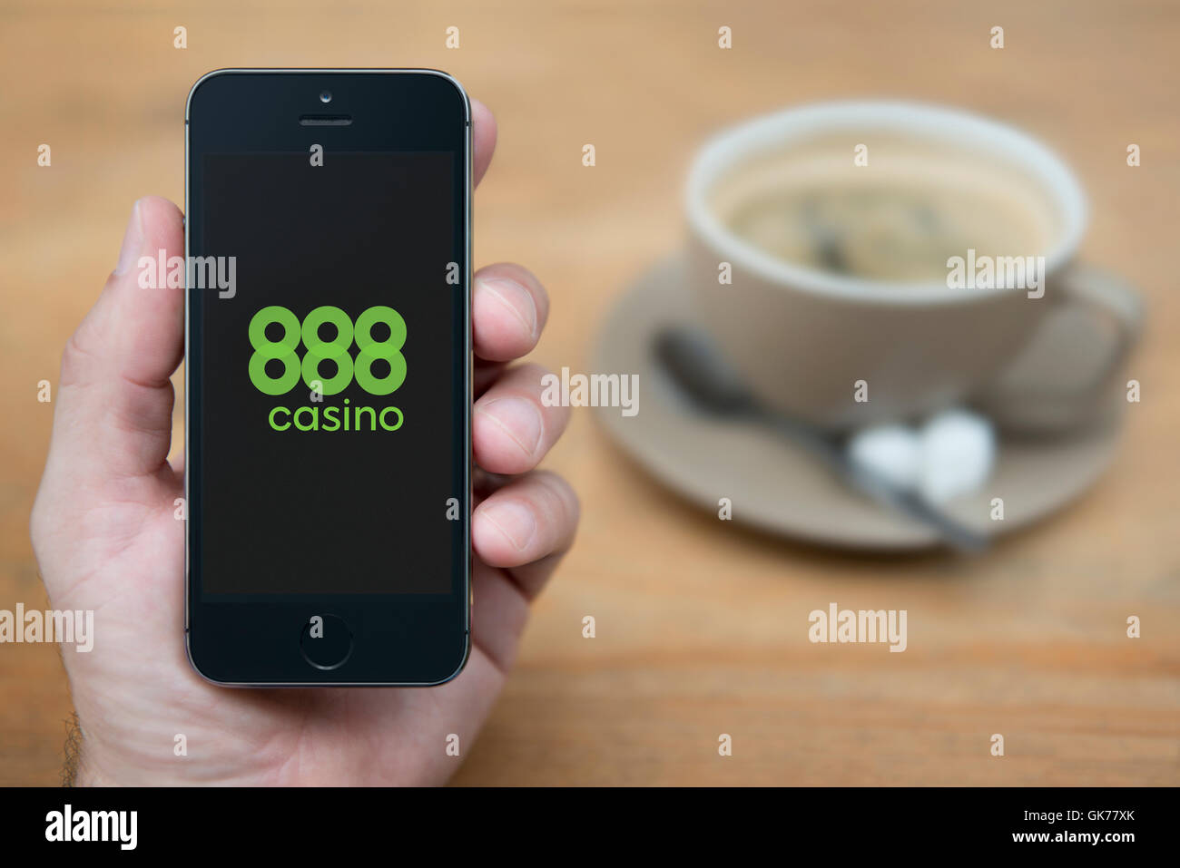 A man looks at his iPhone which displays the 888 Casino logo, while sat with a cup of coffee (Editorial use only). - Stock Image