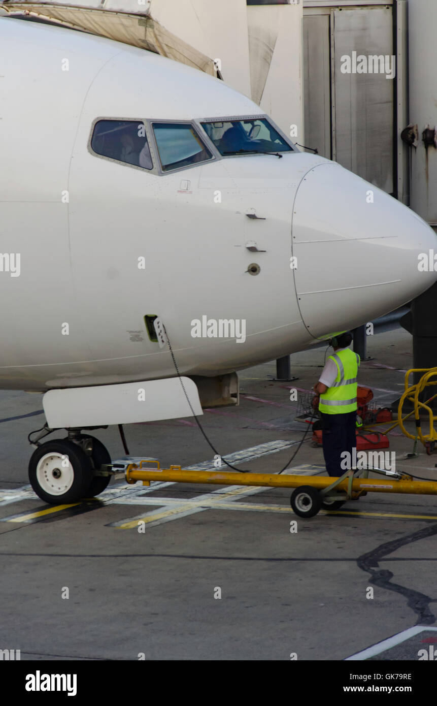 The nose of an airplane being inspected on a runway - Stock Image