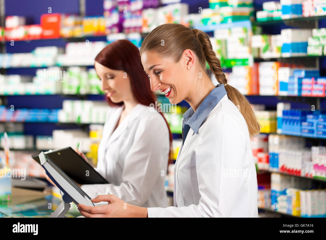 pharmacist with assistant in pharmacy drugstore - Stock Image
