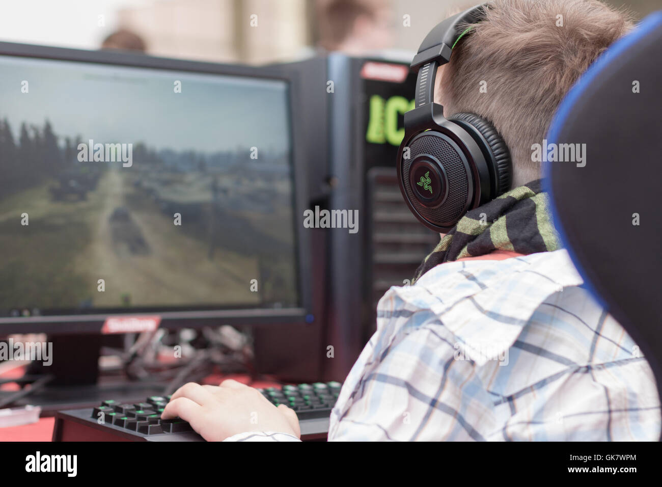 BRNO, CZECH REPUBLIC - APRIL 30, 2016: Young man sits on gaming chair and plays game on PC at Animefest, anime convention - Stock Image