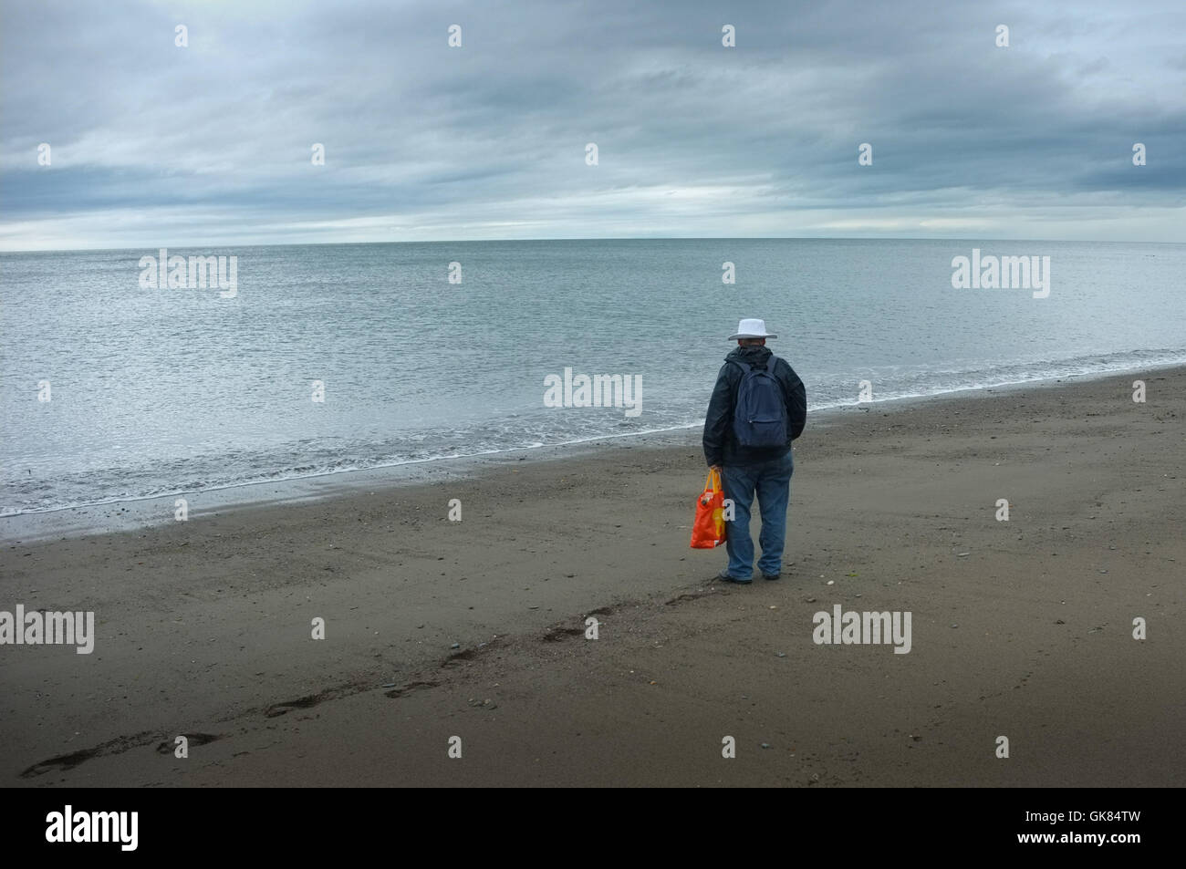 Aberystwyth, Wales, UK. 19th August, 2016.  UK weather: A brave tourist has the beach to himself on a cold grey - Stock Image