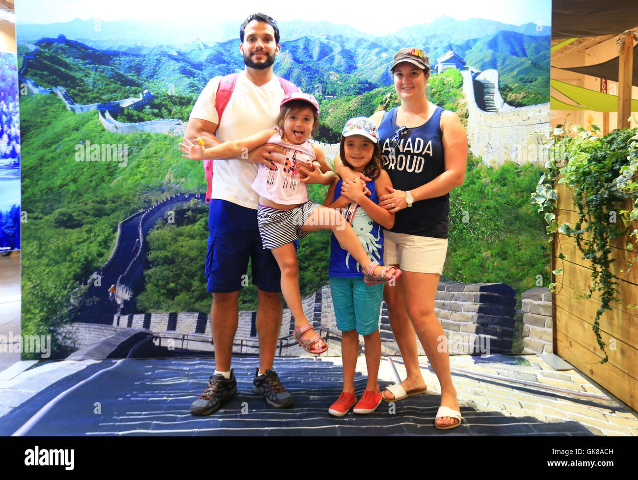 (160819)-- TORONTO, Aug. 19, 2016(Xinhua) -- A family poses for photos in front of a poster of the Great Wall provided - Stock Image