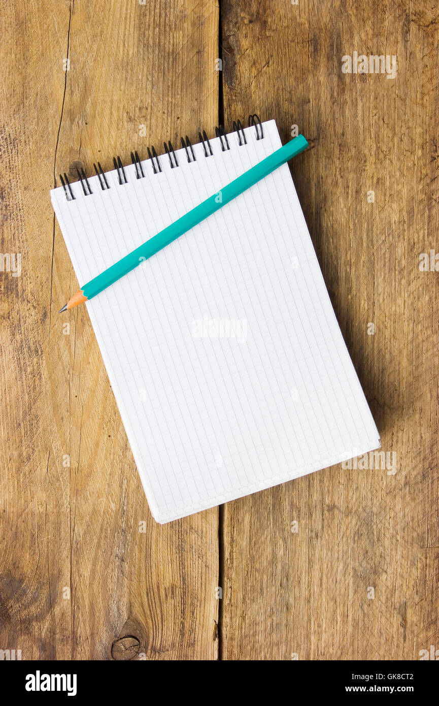 Notepad and pencil on the background of the wooden planks - Stock Image