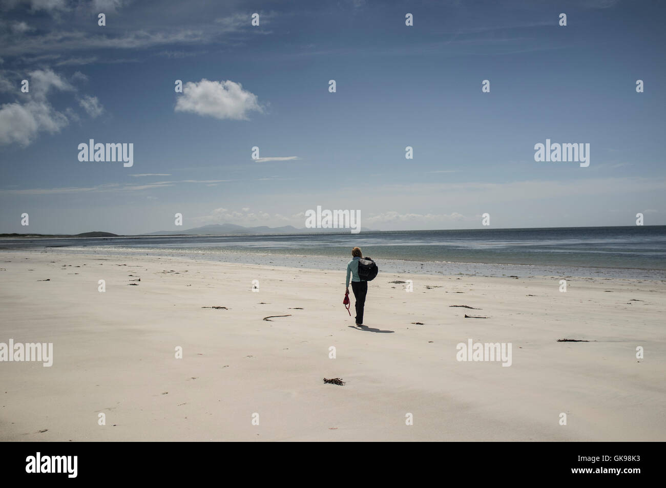 A figure on a large empty beach on the west, Atlantic coast of the Outer Hebrides island of South Uist - Stock Image