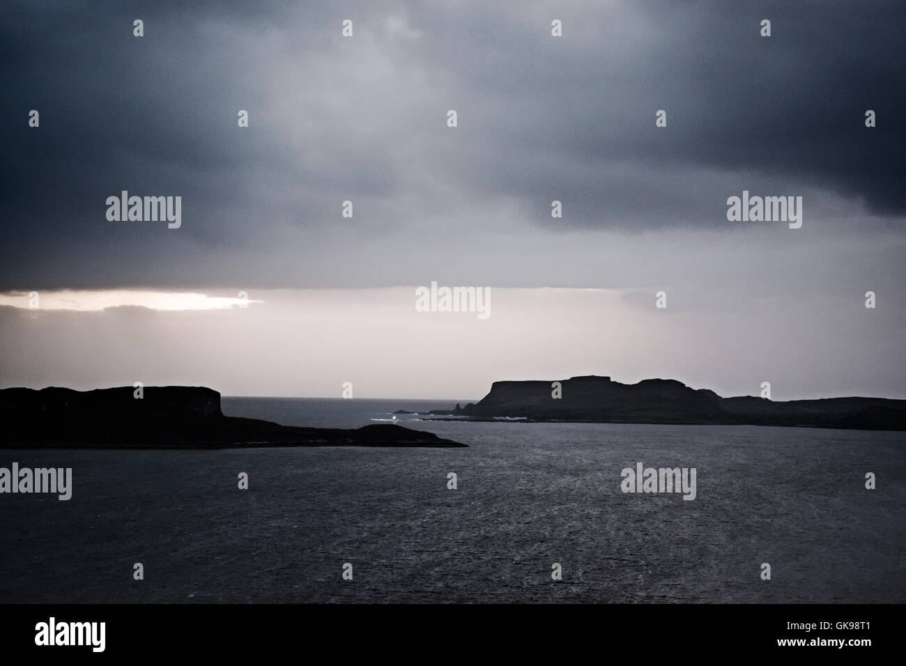Dusk on the west of the island of Skye looking to Ardtreck Point lighthouse and island of Oronsay. Stock Photo
