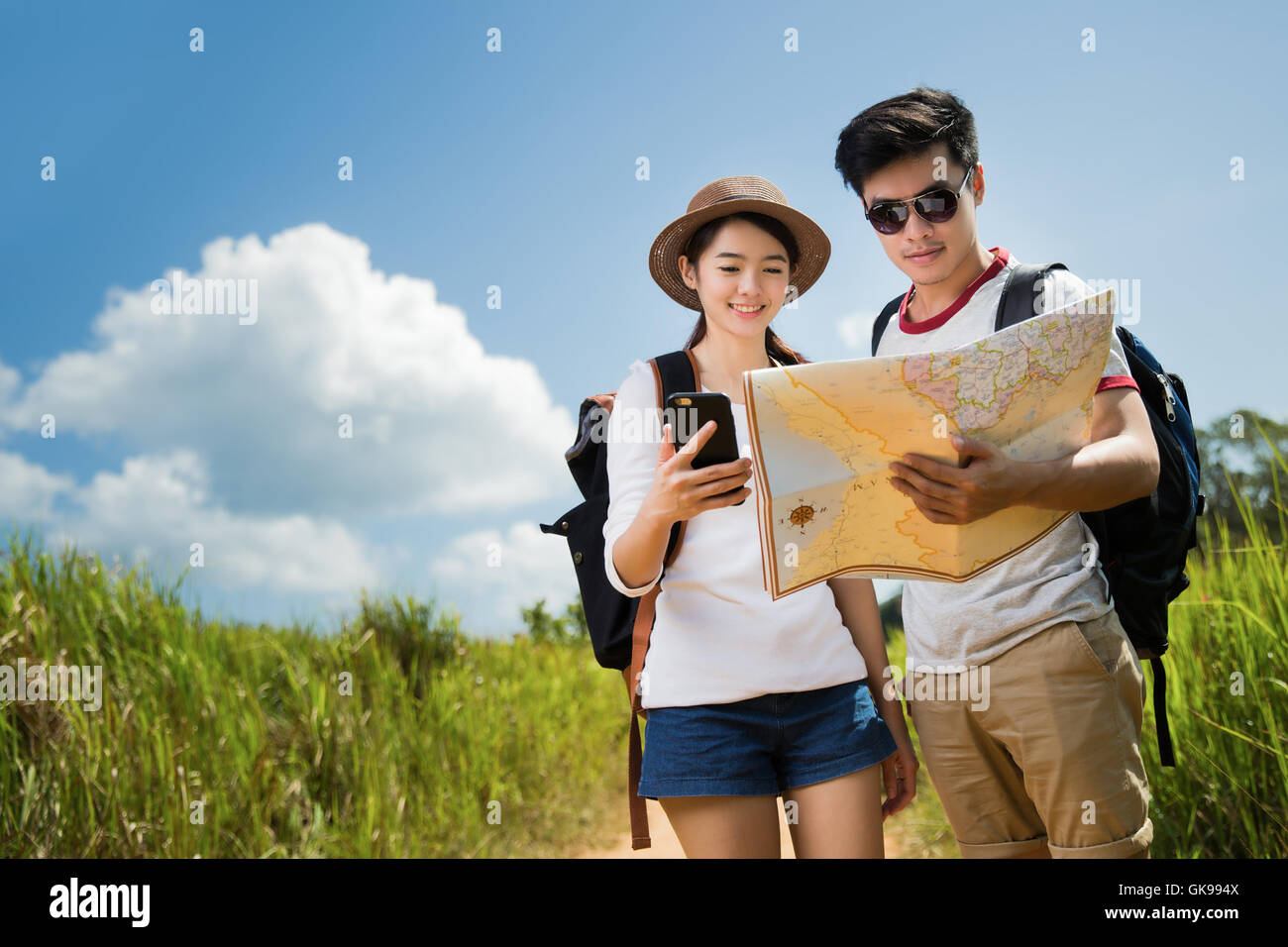Couple tourists opening the map tourist women she is open to