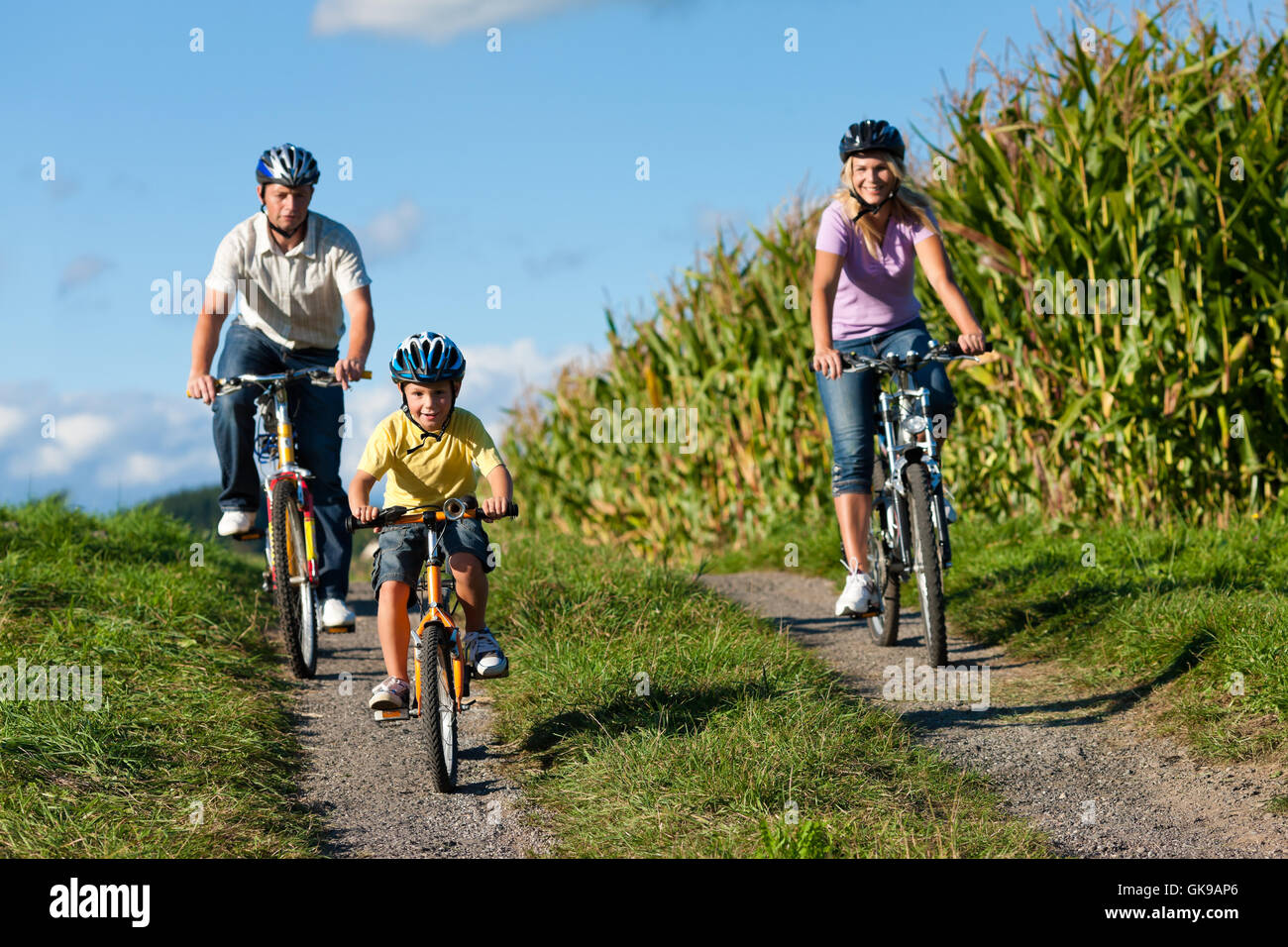 family rides a bike in the summer - Stock Image