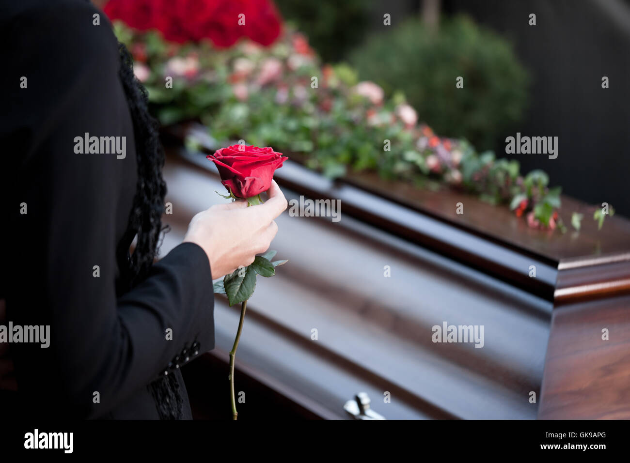 woman at funeral with coffin - Stock Image