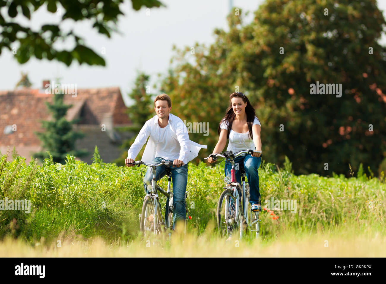 man and woman cycling in summer - Stock Image