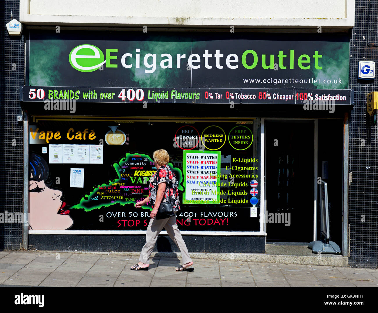 Woman walking past Ecigarette outlet shop, England UK - Stock Image