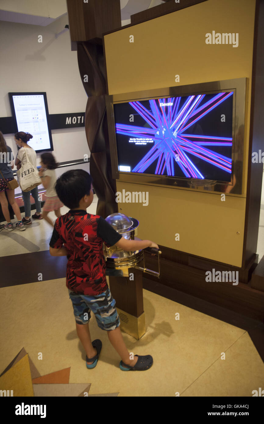 Children and adults explore mathematically based interactive exhibits at the International Museum of Mathematics - Stock Image