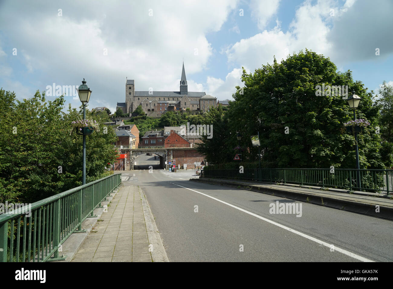 Collégiale saint Ursmer à Lobbes dominates the Skyline in this View from the Bridge over the River Sambre - Stock Image