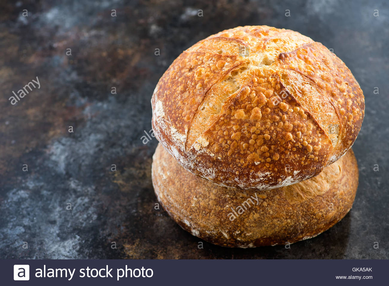Loaves of homemade sourdough bread on dark background, selective focus, copy space - Stock Image