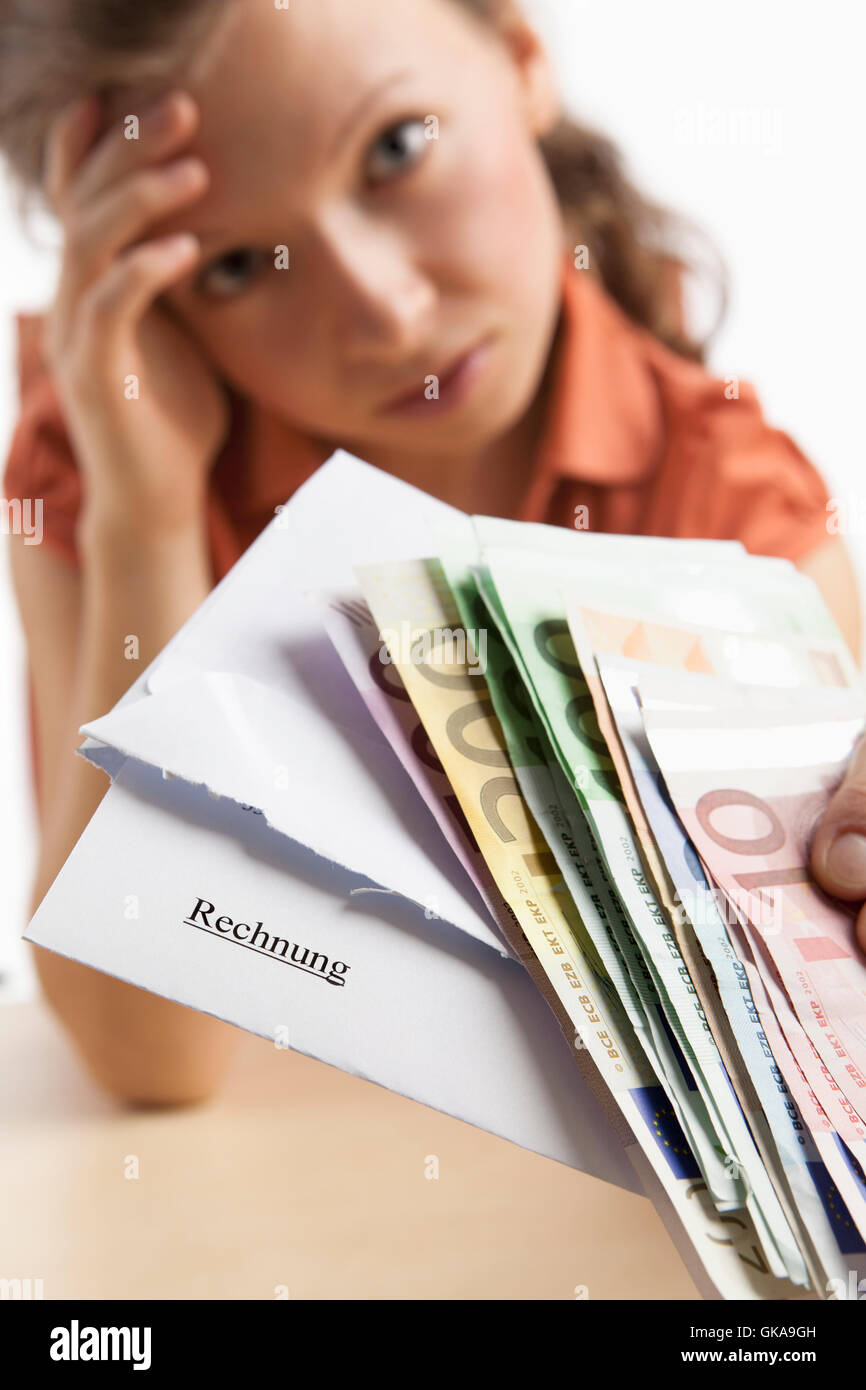 desperate woman holding money and invoice in hand - Stock Image
