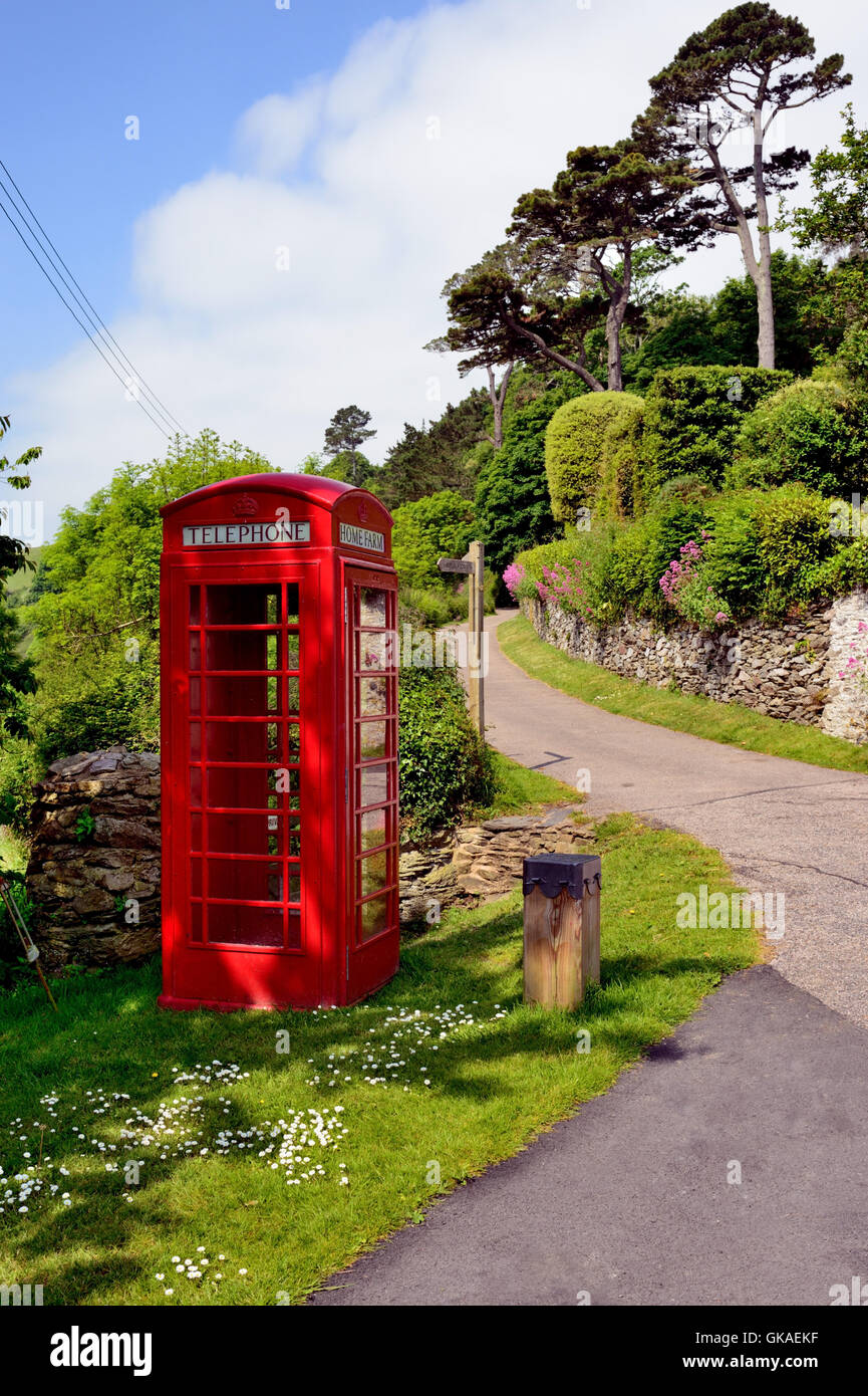 An empty red telephone box beside a country lane in a remote location. - Stock Image