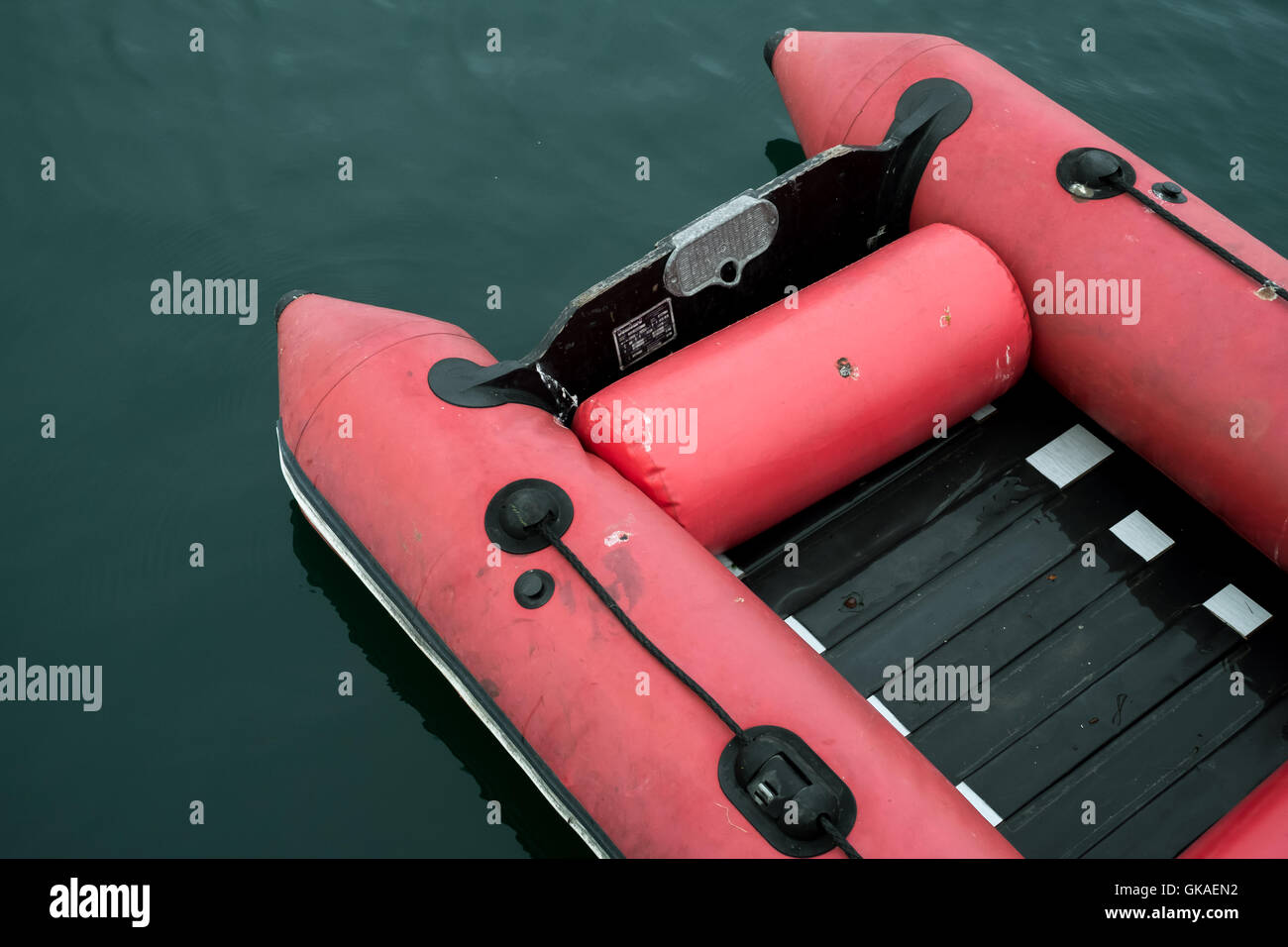 A red rigid inflatable dinghy contrasted against the green waters of the Carrick Roads in Falmouth, Cornwall 19th - Stock Image