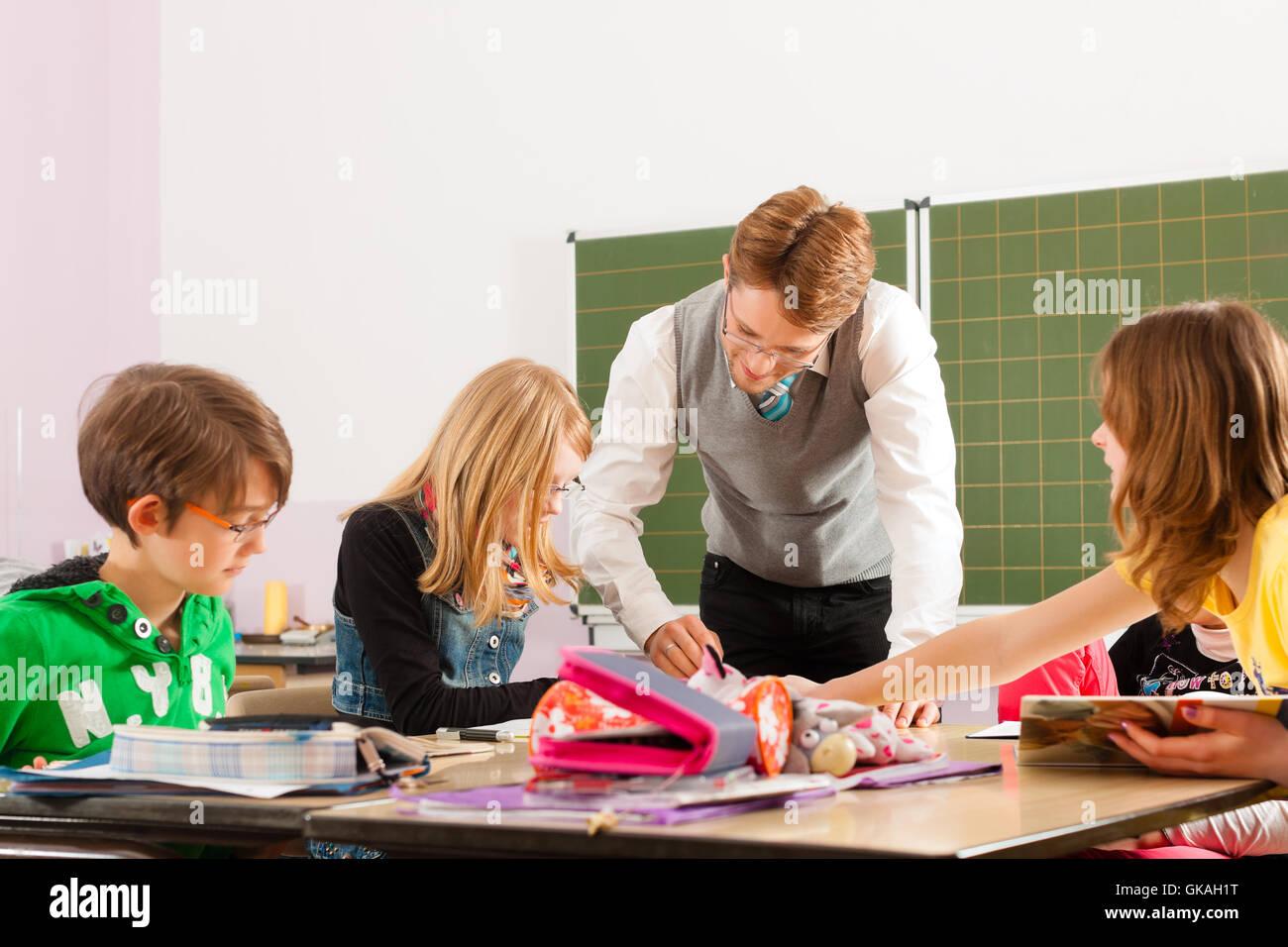 schoolchildren and teacher learning at school Stock Photo