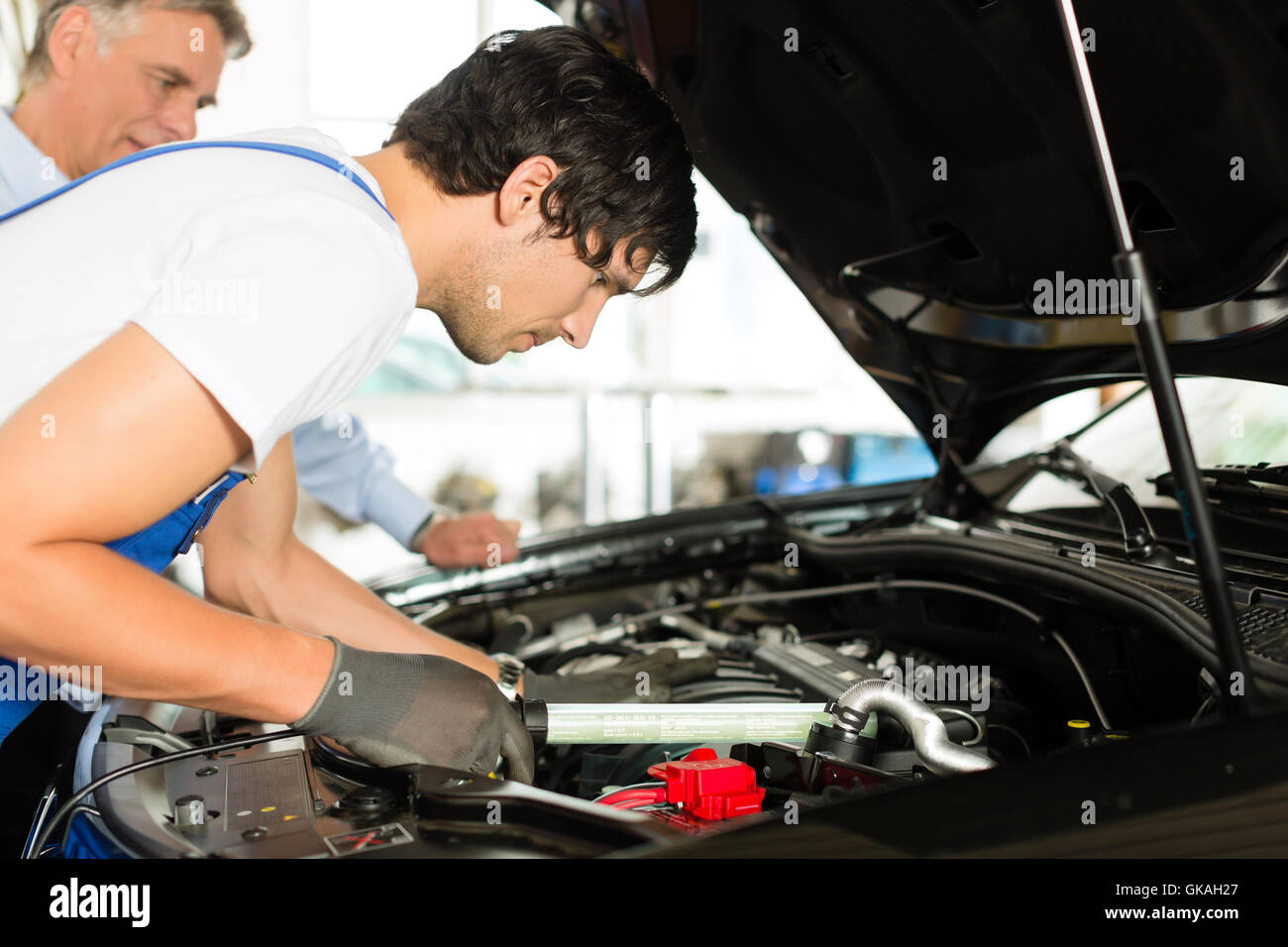 customer and mechanic at car look under the hood - Stock Image