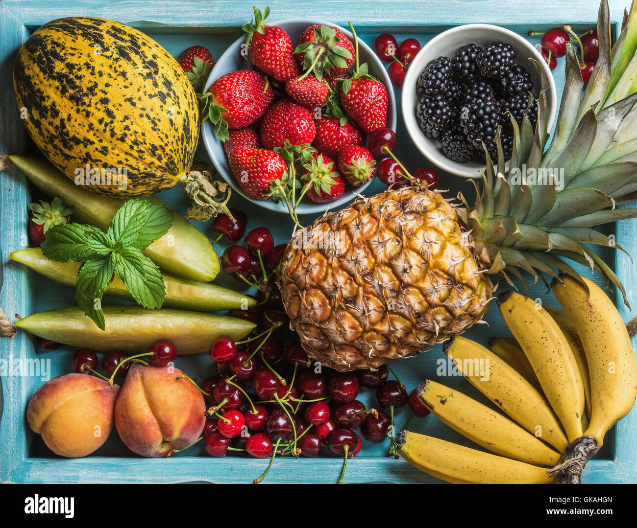 Healthy summer fruit variety. Sweet cherries, strawberries, blackberries, peaches, bananas, melon slices and mint - Stock Image