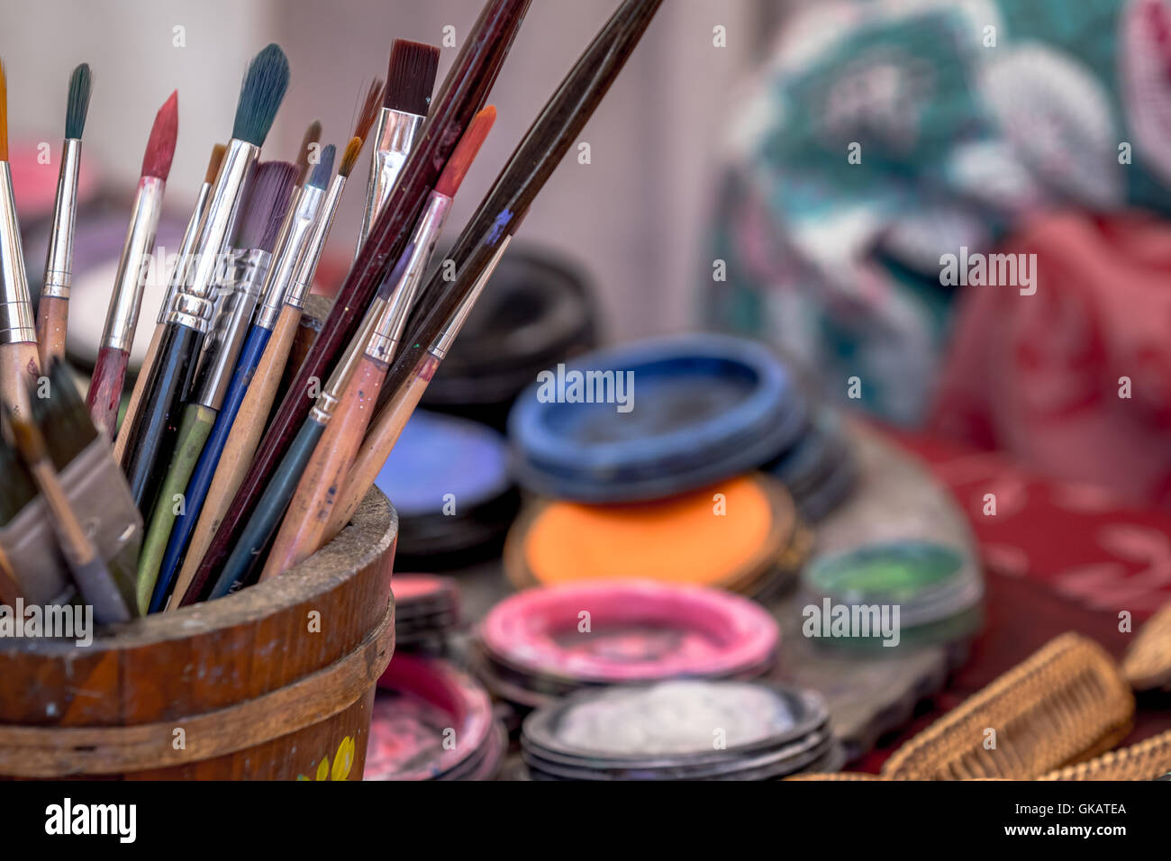 colored paint brushes on a desk - Stock Image