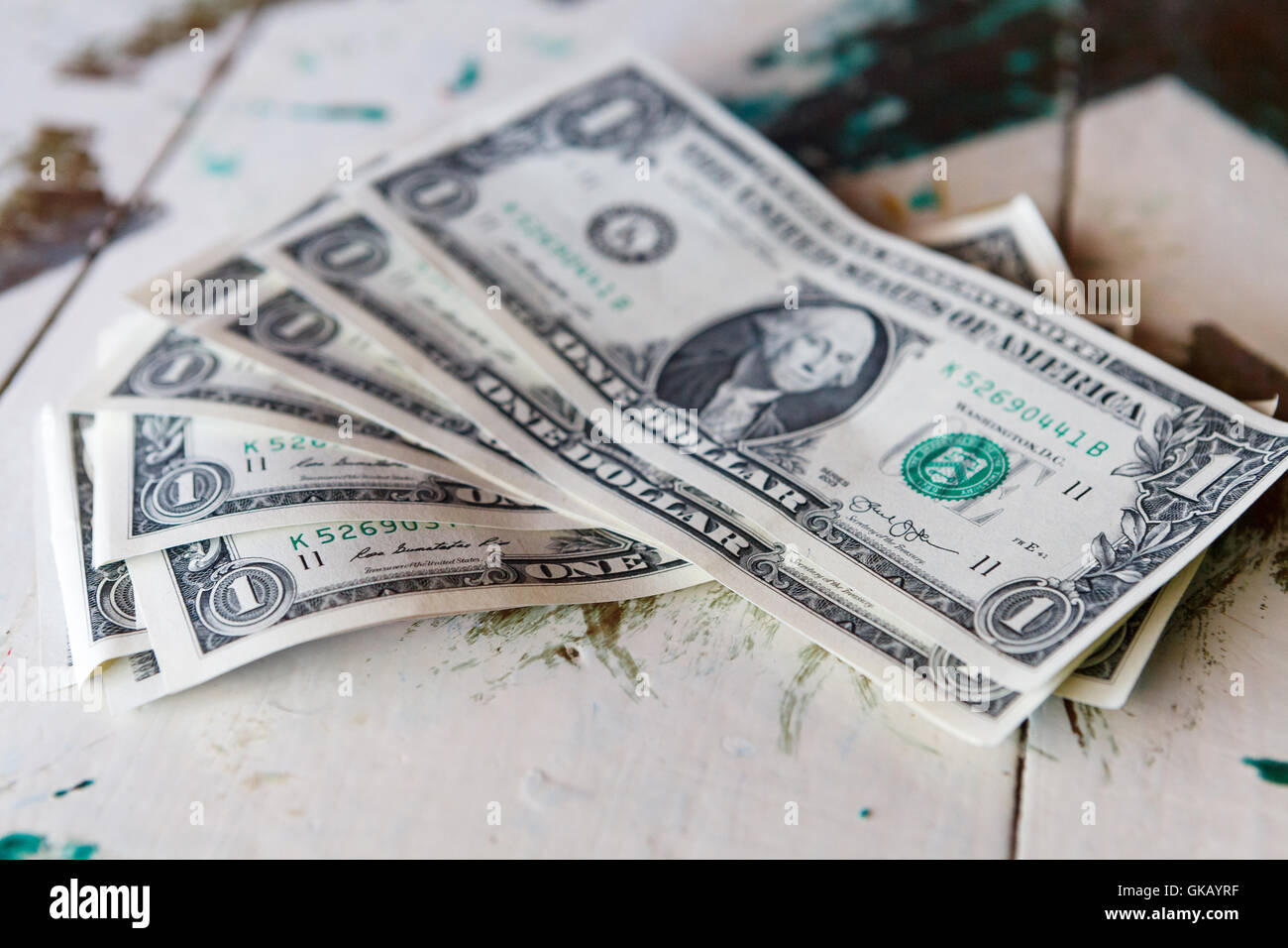 Money - USD one dollar bills on vintage table - Stock Image