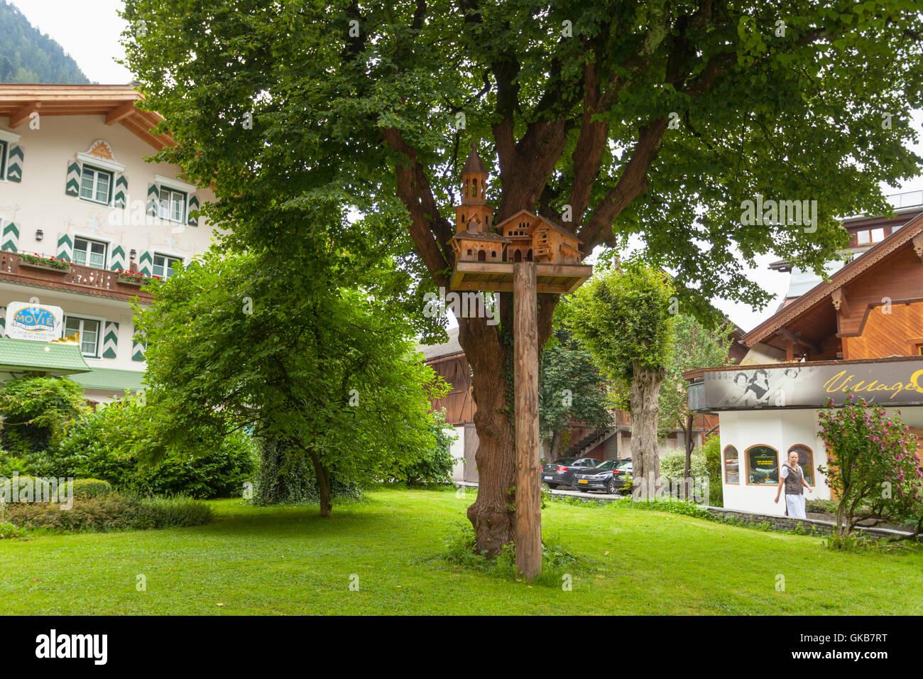 Wooden birdhouse near a tree in Mayrhofen, Austria - Stock Image
