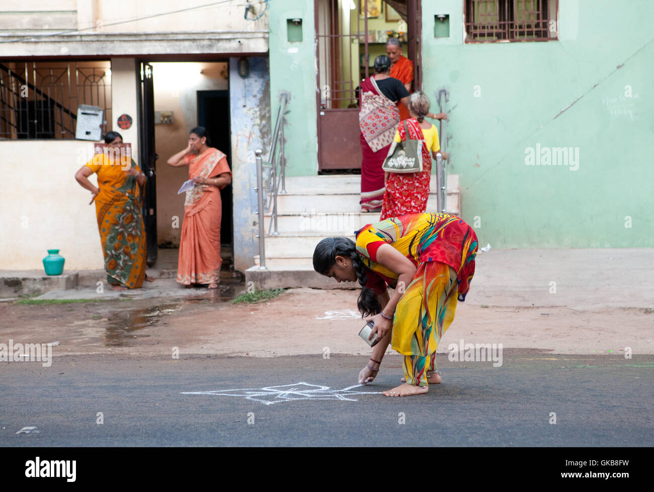 Woman creating rice flour ornament on the asphalt for a religious festival in Tiruchirappalli, India - Stock Image