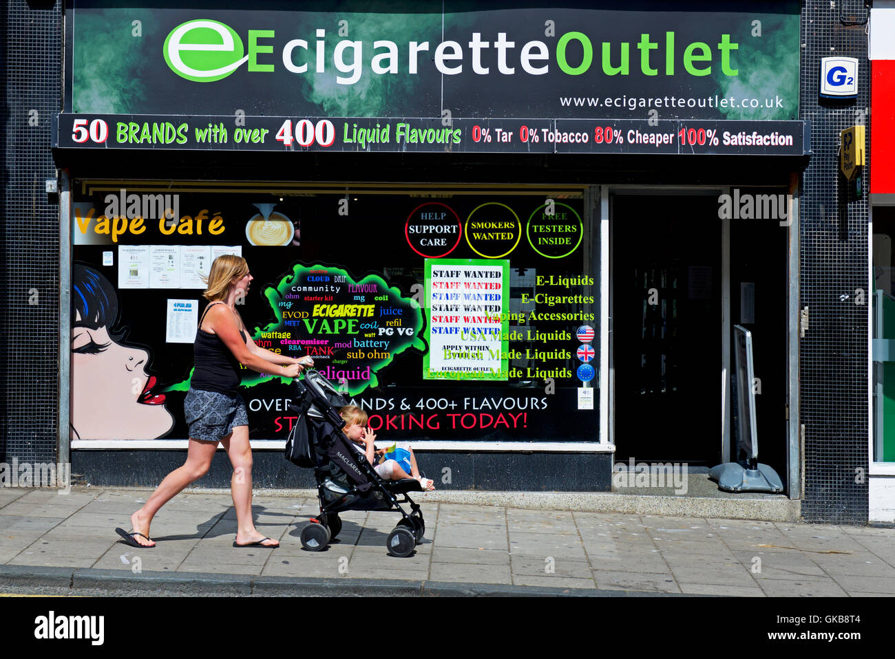 Woman with pushchair walking past Ecigarette outlet shop, England UK - Stock Image