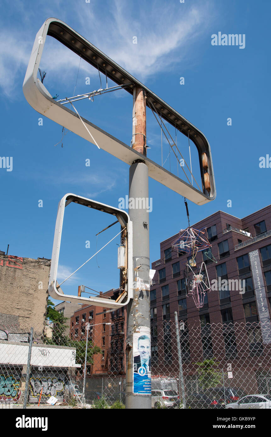 Empty billboard frame with urban art of hanging coathangers and CDs hung from it - Stock Image