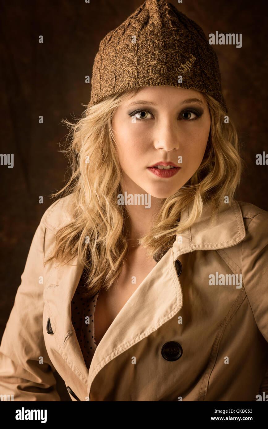 Young blonde model in a winter hat and coat in studio, Virginia Beach, VA Stock Photo