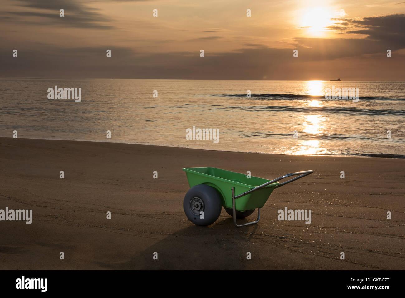 Green beach cart on the beach at sunrise, Virginia Beach, Virginia - Stock Image