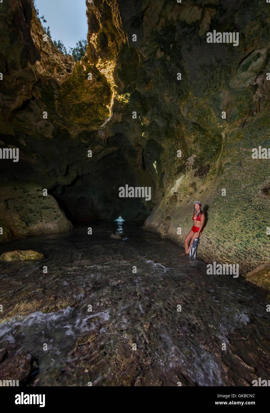 Young woman in a red bikini in a grotto, Rocky Dundas Cay, Exuma Cays, Bahamas Islands - Stock Image