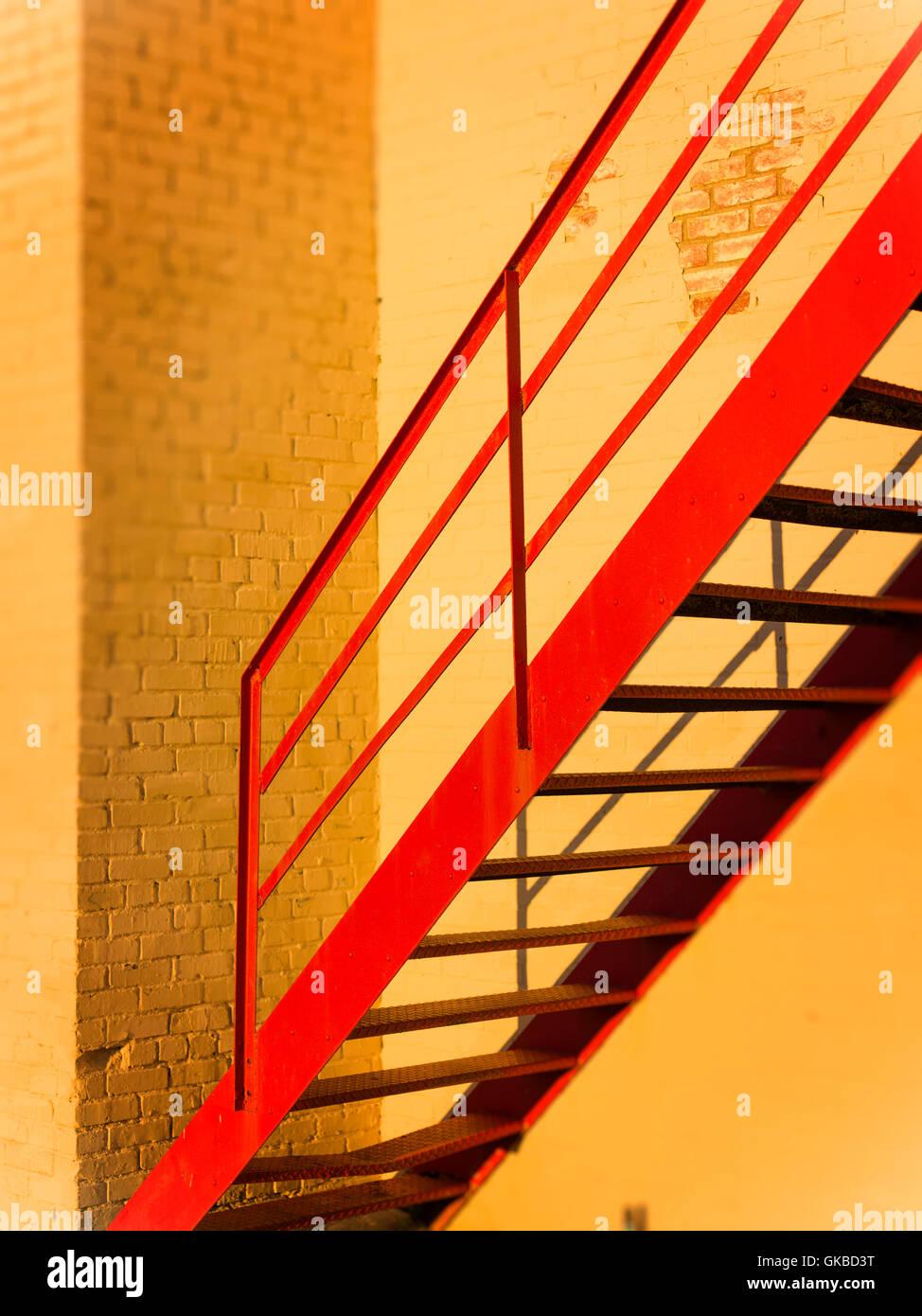 Red stairwell against yellow painted bricks during 'Golden Hour', Virginia Beach, VA - Stock Image