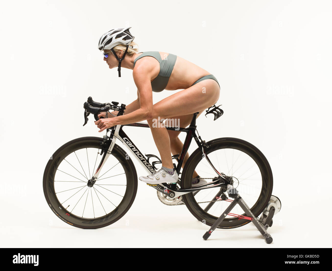 Woman riding her bike on a stationary stand in studio, Virginia Beach, VA - Stock Image