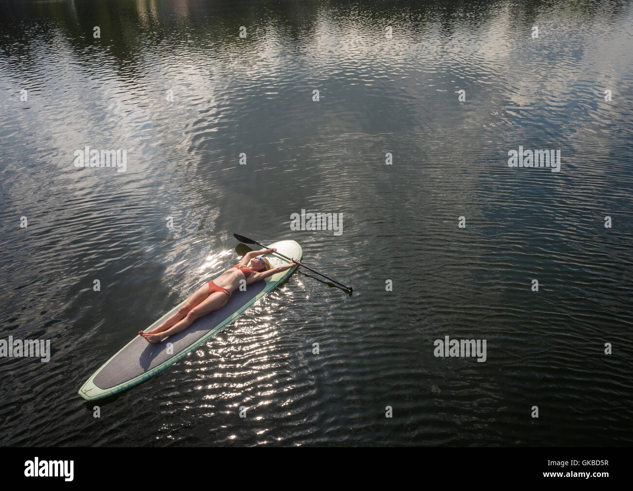 Aerial of a woman laying on a stand up paddle board in Crystal Lake, Virginia Beach, VA - Stock Image